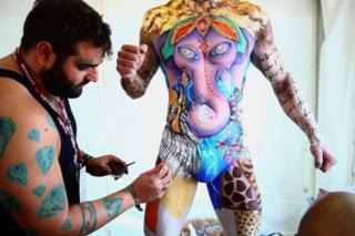 Make-up artist Jonathan Pavan from Brazil works on model Thiago during the World Bodypainting Festival 2018