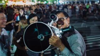 People set up telescopes to witness a rare lunar eclipse near 27 in Taipei, Taiwan