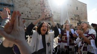 """A member of the liberal Jewish religious movement """"Women of the Wall"""" dances with a Torah scroll at the egalitarian prayer section on the southern side of Judaism's holiest prayer site of the Western Wall in the Old City of Jerusalem on 8 March 2019"""