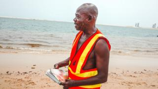 Lifeguard Samuel Omohon holds photos on a beach in Lagos, Nigeria