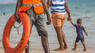 A lifeguard and people strolling on a beach in Lagos, Nigeria
