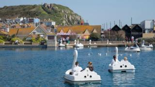 People in a boating lake by the seafront in Hastings