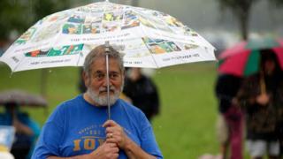 A man stands under an umbrella at the Polk County Steak Fry